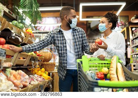 Grocery Shopping. African Family Couple In Masks Buying Vegetables Together Standing With Shop Cart