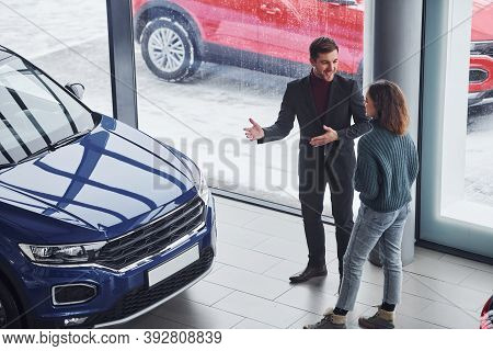 Professional Salesman Assisting Young Girl By Choosing New Modern Automobile Indoors.