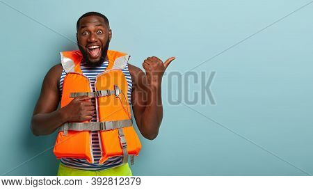 Joyous Dark Skinned Male Rescuer In Orange Life Jacket, Points Aside With Thumb, Feels Glad To Rescu