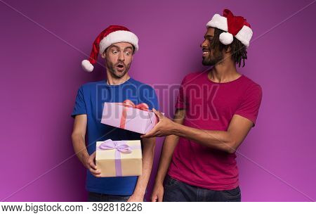 Amazed Friends Happy By The Arrival Of Christmas With Present. Purple Background