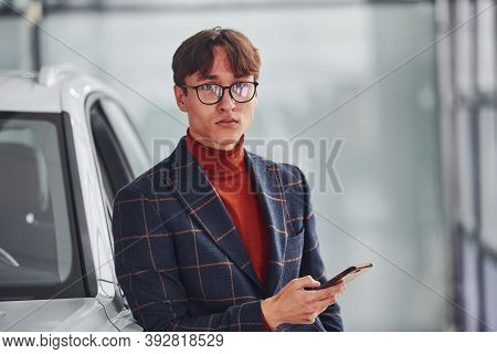 Hipster In Formal Wear And In Eyewear Standing Near White Modern Car Indoors.