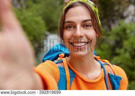 Tourist Female Hiker Makes Selfie Portrait, Smiles At Camera, Stands Outdoor Near Nature Outlook, We