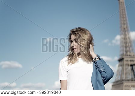 Woman At Eiffel Tower In Paris, France On Blue Sky. Girl Traveler With Blond Hair On Sunny Day. Arch