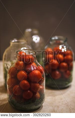 Preparing Tomatoes For Conservation In Glass Jars. Pickled Tomato In Glass Jar. Glass Jar With Tomat