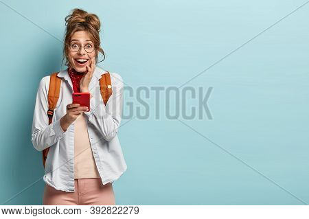 Happy Surprised Teenager Looks Gladfully, Holds Red Cell Phone, Receives Income Message, Wears Casua