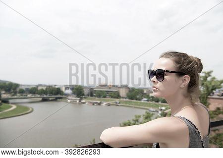 Woman Look At Vistula River In Krakow, Poland. Sensual Woman In Sunglasses On Sunny Day. Summer Vaca
