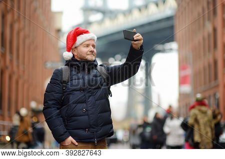 Middle Aged Man Tourist In Santa Claus Hat Takes Selfie On Street Near The Manhattan Bridge In New Y