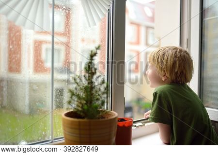 Little Boy Watching The Rain Outside At Opened Window. Bad Weather - Wind And Downpour. Child Boring