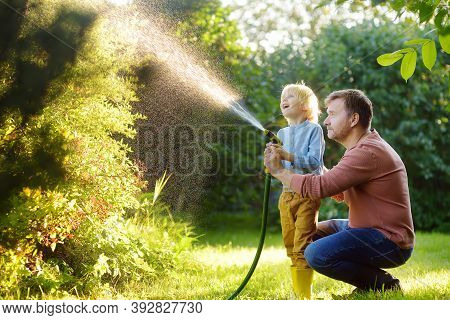 Funny Little Boy With His Father Watering Plants And Playing With Garden Hose In Sunny Backyard. Pre