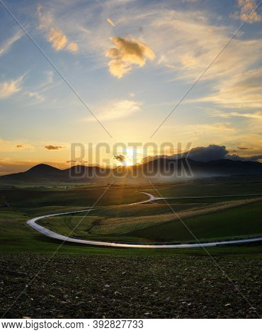 winding road in a rural valley of Sicily at the sunset