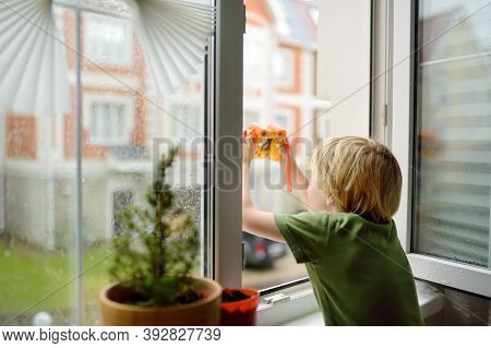 Little Boy Watching The Rain Outside At Opened Window And Taking Photo. Bad Weather - Wind And Downp