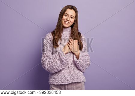 Portrait Of Happy Young European Woman Keeps Hands On Breast, Shows Heart Gesture, Expresses Gratitu