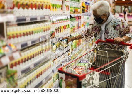 Old Woman Wearing A Protective Mask In Food Shopping Store During Covid-19.