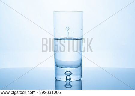 Water Drop Splash Inside Glass Half Full Against Bright Background. Purity And Health Concept