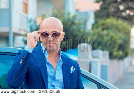 Young Handsome Man Holding Touching Sunglasses Posing Near His Car In A Blue Navy Suit Outside Stand