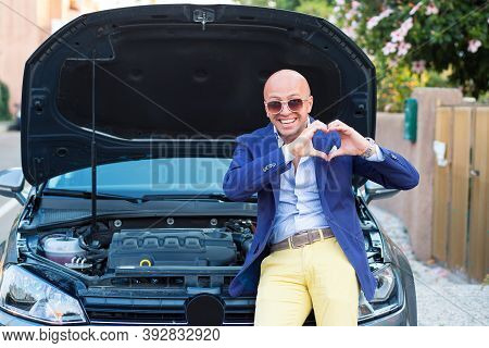 I Love My Engine Car. Handsome Man Showing Heart Hand Gesture Standing Near His New Car With Open Ho