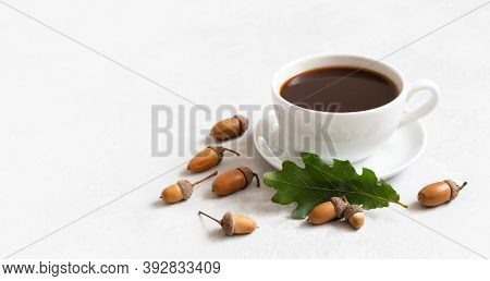 Small Cup Of Black Coffee, Oak Leaf And Acorns On A White Background. Acorn Coffee Without Caffeine.
