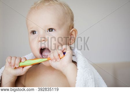 Cute Child Kid Boy Covered With A Towel Brushing His Teeth. Health Care, Dental Hygiene, People And