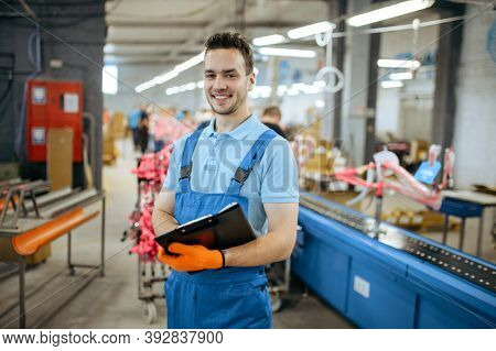 Bicycle factory, smiling worker at assembly line