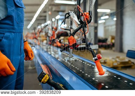 Bicycle factory, worker checks bike assembly line