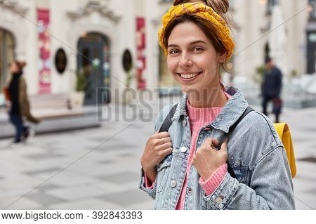 Cropped Image Of Cheerful Young Caucasian Woman Strolls Across City With Small Rucksack, Wears Yello