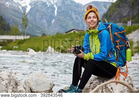 Glad Optimistic Female Tourist Rests Outdoor On Rock, Enjoys Beautiful View Of Small Mountain River