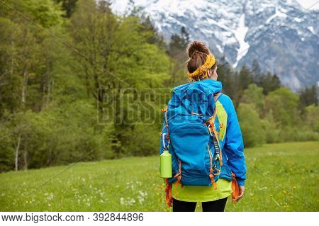 Trekking, Wandering And Hiking Concept. Active Woman Hiker Poses On Hilltop, Strolls Against Mountai