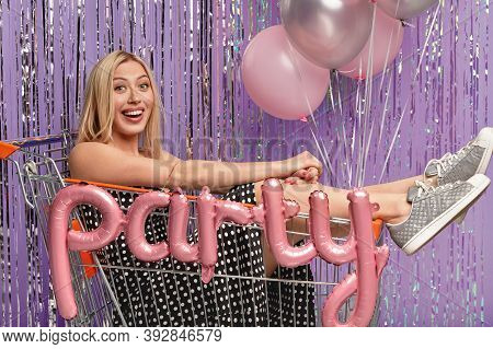Horizontal Shot Of Optimistic Blonde Woman Has Fun At Birthday Party, Poses In Shopping Cart, Wears