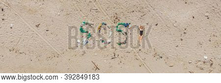 Sos Inscription And Woman Sunbathes On The Beach Nearby. Environmental Problem. Ecology Concept. Pla