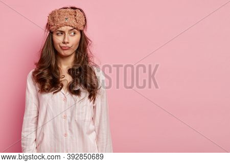 Photo Of Thoughtful Relaxed Young Woman Has Curly Hair, Wears Eyemask, Slumber Suit, Concentrated As