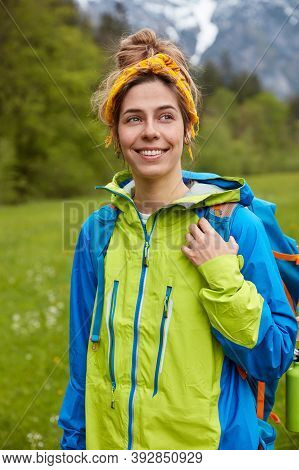 Optimistic Lovely Traveler With Glad Expression, Wears Blue And Green Anorak, Carries Backpack, Stan