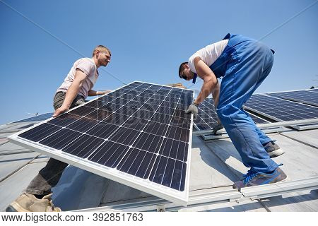 Male Workers Installing Solar Photovoltaic Panel System. Electricians Lifting Blue Solar Module On R