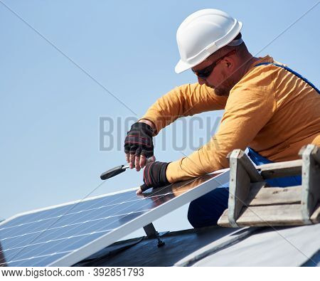 Man Engineer In Protective Helmet Installing Stand-alone Solar Photovoltaic Panel System Using Screw