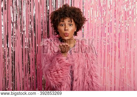 Lovely Fashionable Afro American Woman In Fur Pink Coat, Makes Hand Gesture, Sends Air Kiss, Poses A