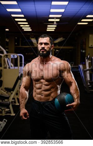 Strong Young Bearded Male With Powerful Abdominal Muscle Holding Heavy Training Ball In Dark Night S