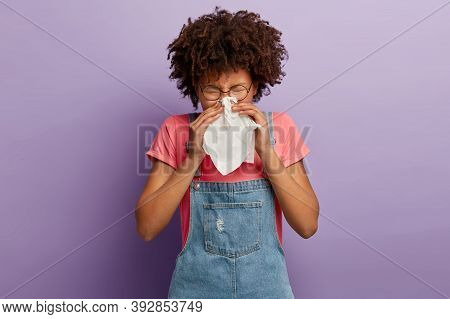 Curly Young Female Feels Unwell, Blows Nose In White Tissue, Suffers From Running Nose, Cold Symptom