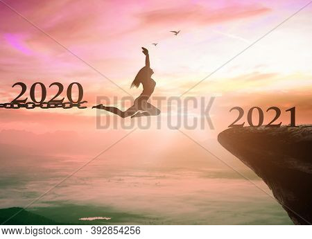 Success New Year 2021 Concept: Silhouette Woman Jump Broken Chains With 2020 To 2021 Years On Sunset