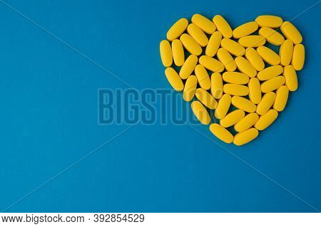 Yellow Pills Health Medication Tablets In Heart Shape Lying On Blue Vivid Surface With Copy Space