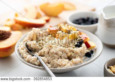 Oatmeal Bowl With Hemp Seeds, Peach And Raisins. Healthy Vegan Breakfast Food. Oatmeal Porridge
