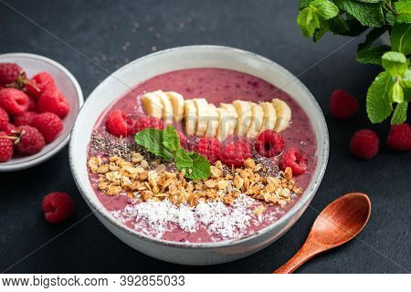 Pink Smoothie Bowl With Raspberry, Banana, Granola And Coconut On A Black Background, Closeup View.