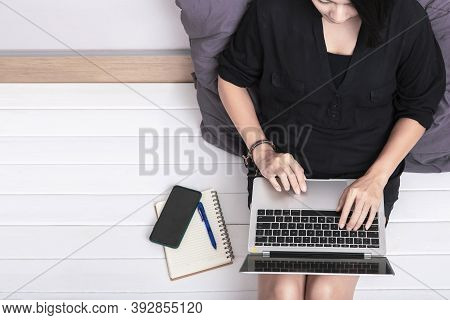 Top View Of A Young Asian Woman Using Laptop Computer Sitting On Wooden Floor At Home , Work From Ho