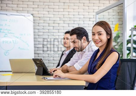 Business Asian Woman Turns Around Smiling Confidently While Coworker In The Background In The Office