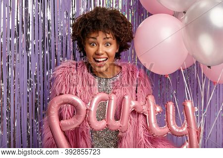 Joyous Curly Dark Skinned Woman In Pink Coat, Carries Balloons, Satisfied With Party Celebration, Ha