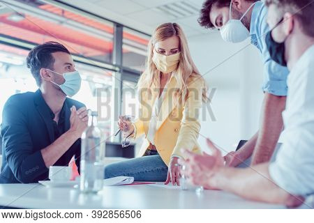 Business team in the office negotiating an agreement wearing face masks