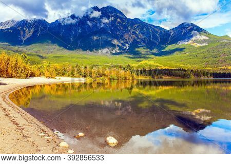 Rocky Mountains of Canada. Smooth water of the lake reflects Pyramid Mountain  and lush cumulus clouds. Pyramid Lake. Active eco and photo tourism concept