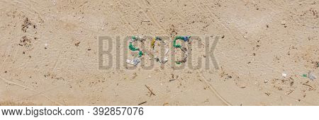 Environmental Problem. Ecology Concept. Plastic On The Beach With Sos Writing. Spilled Garbage On Th