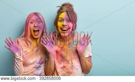 Joyous Best Female Friends Laugh And Have Fun Together, Show Palms, Smeared With Colorful Powder, Ce