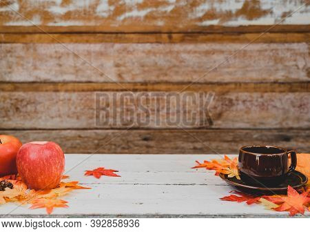 Autumn And Fall Season. Hot Coffee With Fake Maple Leaf On Wood Table. Harvest Cornucopia And Thanks