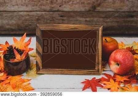 Autumn And Fall Season. Empty Photo Frame And Fake Maple Leaf On Wood Table. Harvest Cornucopia And