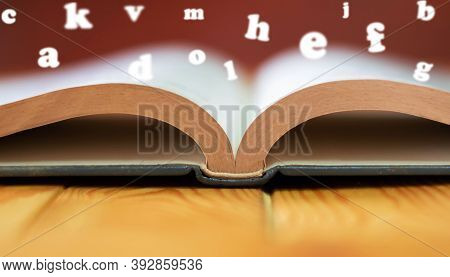 Close Up Textbook On Wooden Table With Copy Space And Blurred English Alphabets Floating Over Book P